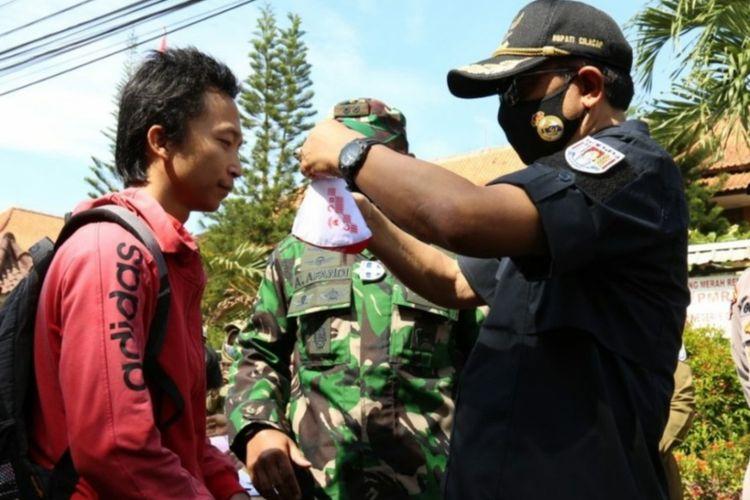 Bupati Cilacap Tatto Suwarto Pamuji memberikan masker kepada warga di Cilacap, Jawa Tengah, Selasa (2/2/2021).