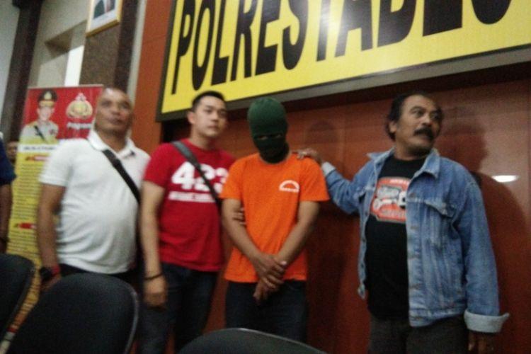 Dodik Ikhwanto (21), pelaku penghina Iriana Joko Widodo hanya tertunduk lesu saat digiring anggota Satreskrim Polrestabes Bandung, Senin (12/9/2017).