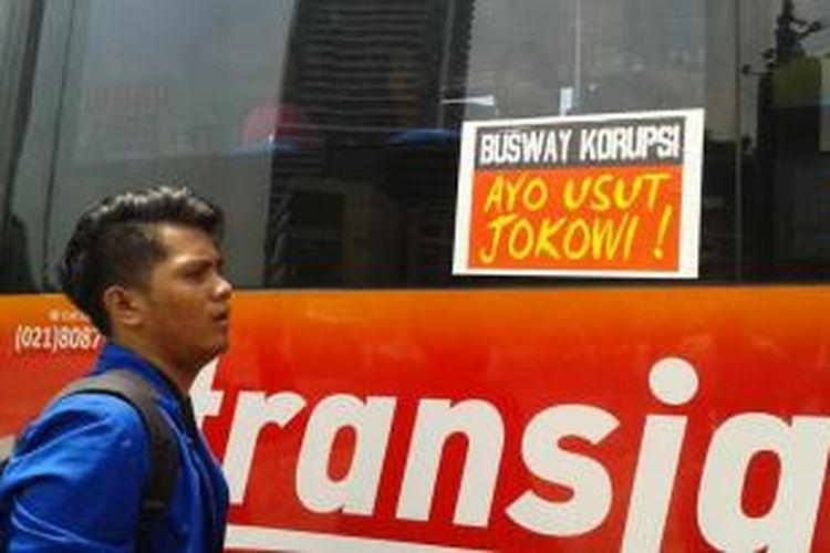 Sekitar 20 orang mahasiswa menghentikan dan menempel stiker bertuliskan 'Busway Korupsi Ayo Usut Jokowi!' di bus transjakarta yang mengarah ke Blok M, pada Selasa (1/4/2014) di Bundaran HI, Jakarta.