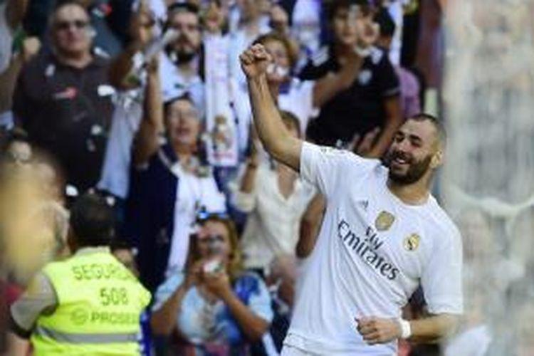 Penyerang Real Madrid Karim Benzema melakukan selebrasi setelah mencetak gol ke gawang Granada pada pertandingan La Liga di Santiago Bernabeu, Sabtu (19/9/2015).