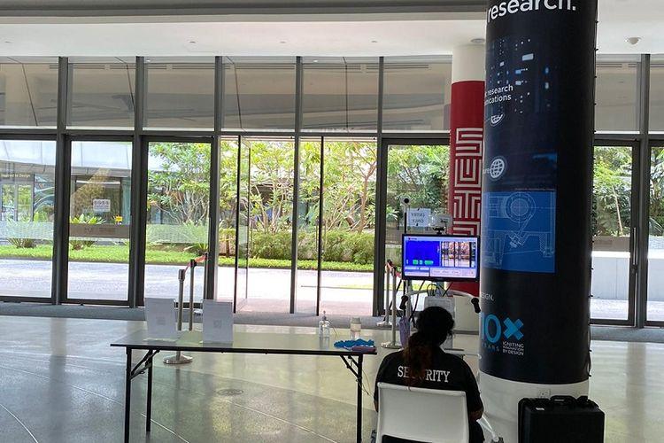 Suasana Singapore University of Technology and Design (SUTD) di Changi, Singapura di mana terlihat seorang petugas sedang duduk memantau pengecekan suhu tubuh