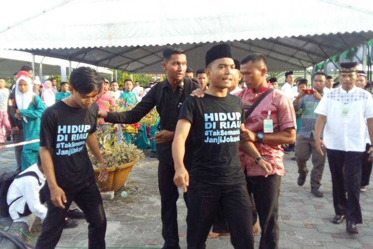 Dua mahasiswa saat diamankan petugas karena melakukan orasi saat Presiden Joko Widodo (Jokowi) memberikan sambutan dalam acara Harlah NU ke-92 di Pekanbaru, Riau, Rabu (9/5/2018).
