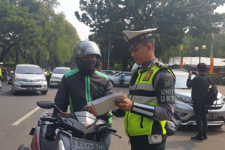 Polisi menilang pengendara sepeda motor yang belum membayar pajak kendaraan bermotor (PKB)-nya di Jalan Lapangan Banteng Selatan, Jakarta Pusat, Jumat (11/8/2017).