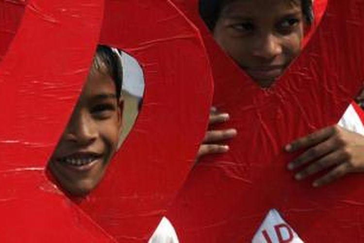 Anak-anak dan akitivis sosial turut ambil bagian dalam kampanye Hari AIDS Sedunia di Kolkata, India, Minggu (30/11/2014).