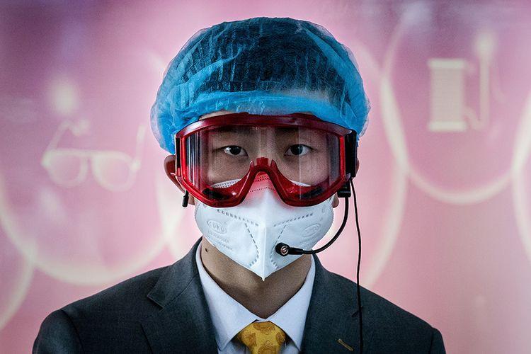 Seorang pekerja bagian informasi mengenakan penutup kepala, kacamata pelindung, dan masker, sebagai tindakan pencegahan terhadap virus corona (Covid-19) di area kedatangan Bandara Ibu Kota Beijing di China, Senin (16/3/2020).