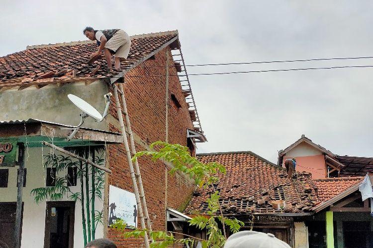 Warga memperbaiki atap rumah yang rusak diterjang puting beliung di Kecamatan Margadana, Kota Tegal, Jumat (26/2/2021)