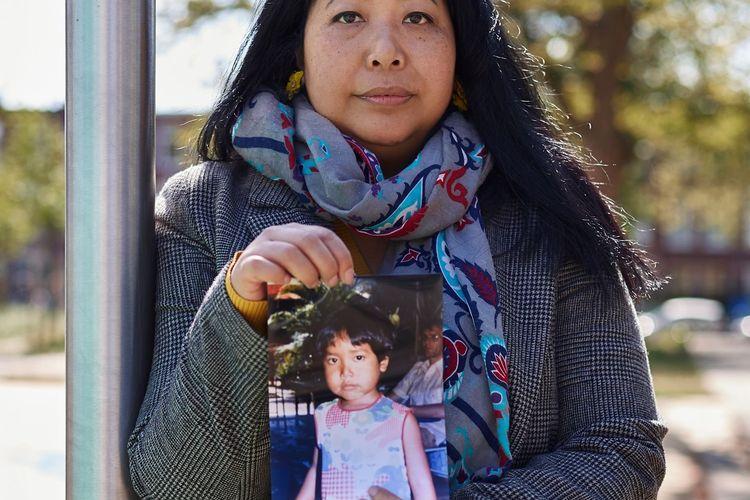 Widya berpose dengan fotonya semasa kecil dalam upaya pencariannya terhadap ibu kandungnya di Indonesia.