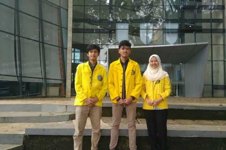 Muhamad Iqbal Januadi Putra, Fida Afdhalia, dan Diki Nurul Huda berfoto di depan Perpustakaan UI.