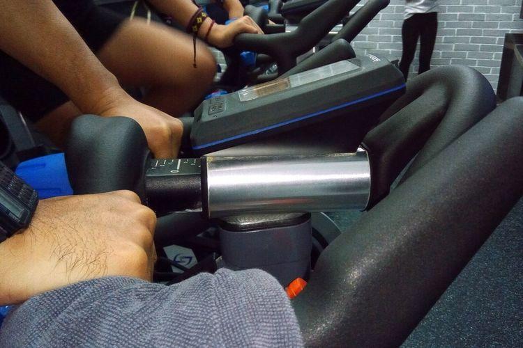 Foto berlatih sepeda statis. Pada panel sepeda bagian depan sudah tersedia fitur-fitur  data.