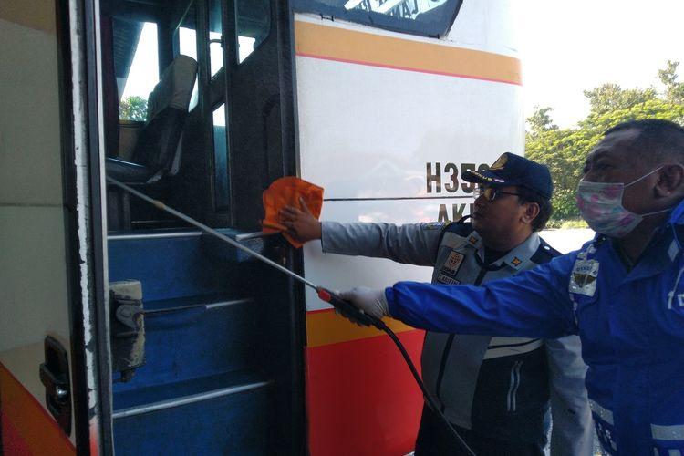 Petugas dari Dinas Perhubungan Kabupaten Jombang, Jawa Timur, saat membersihkan armada bus dan menyemprotkan disinfektan sebagai upaya pencegahan penularan virus corona melalui sarana transportasi publik, Jumat (20/03/2020).