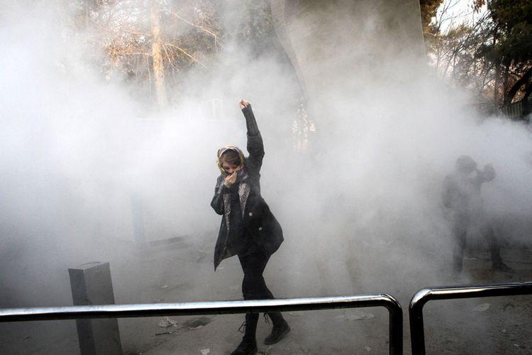 Seorang wanita mengangkat tangannya di tengah kepulan gas air mata saat mengikuti aksi demo di Universitas Teheran, Ibu Kota Teheran, Sabtu (30/12/2017). Unjuk rasa anti-pemerintahan Presiden Hassan Rouhani di Iran berlangsung hampir sepekan, memakan korban tewas hingga puluhan orang dan ratusan orang ditangkap pihak keamanan.