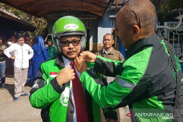 Anggota DPRD Jember terpilih periode 2019-2024 Agusta Jaka Purwana (kiri) naik ojek dari rumahnya menuju ke Gedung DPRD Jember untuk menghadiri pelantikannya di Gedung DPRD Kabupaten Jember, Jawa Timur, Rabu (21/8/2019)