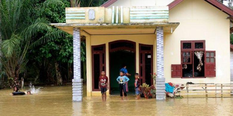 Anak-anak bermain di depan rumahnya yang terendam banjir di Desa Blang Luah, Kecamatan Woyla Timur, Aceh Barat, 24 Oktober lalu. Intensitas hujan yang tinggi menyebabkan kawasan itu dilanda banjir.