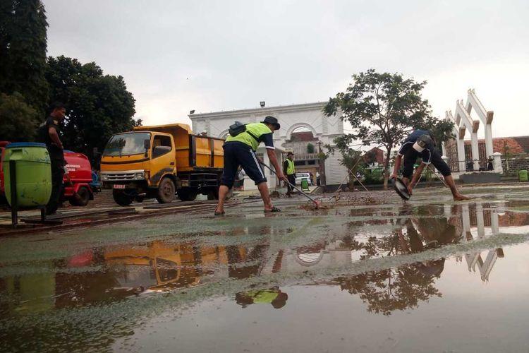 Sejumlah petugas tengah membersihkan air campur lumpur yang menutupi rumput sintetis di dalam kawasan alun-alun Cianjur, Kamis (23/01/2020) petang. Landmark Cianjur itu diresmikan Presiden Jokowi awal Februari 2019.