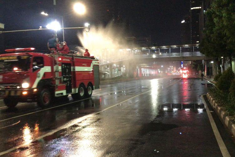 Anggota Suku Dinas Penanggulangan Kebakaran dan Penyelamatan DKI Jakarta menyemprotkan cairan disinfektan di sekitar Jalan Jenderal Sudirman-MH Thamrin, Jakarta pada Kamis (32/12/2020) malam.