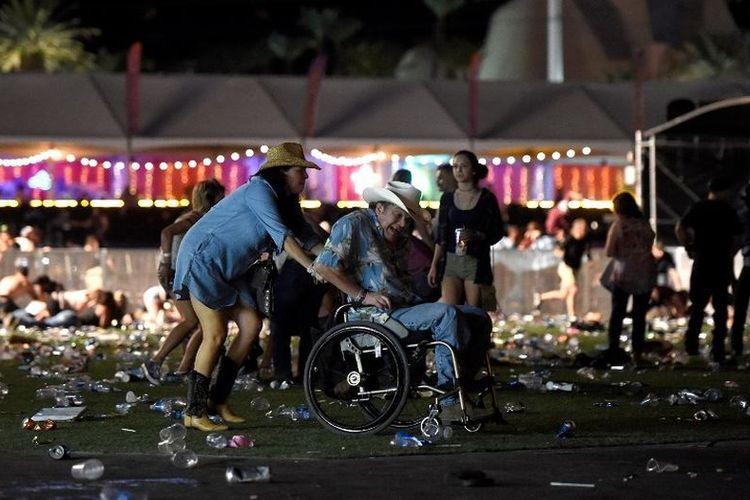 Seorang pria dengan kursi roda dibawa keluar dari festival musik country Route 91 Harvest setelah terjadi terdengar suara tembakan di Las Vegas, Nevada, Minggu (1/10/2017). Pelaku penembakan diduga berada di sekitar Mandalay Bay Resort and Casino.