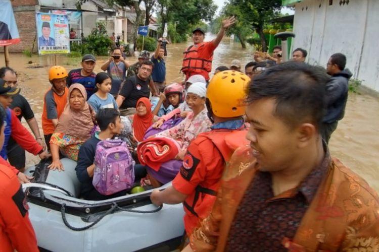EVAKUASI-Tim Sar gabungan mengevakuasi siswa (berhelm) dan warga yang terdampak banjir di Desa Jerukgulung, Kecamatan Balerejo, Kabupaten Madiun, Jawa Timur, Rabu ( 6 / 3 / 2019) sore. Hingga malam ini bencana banjir makin meluas hingga delapan kecamatan di Kabupaten Madiun.