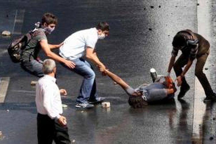 Para demonstran membantu rekan mereka yang terluka dalam bentrokan dengan polisi antihuru-hara di Ankara, 1 Juni 2013. Polisi memblokir sekelompok demonstran yang berbaris menuju parlemen dan kantor perdana menteri.
