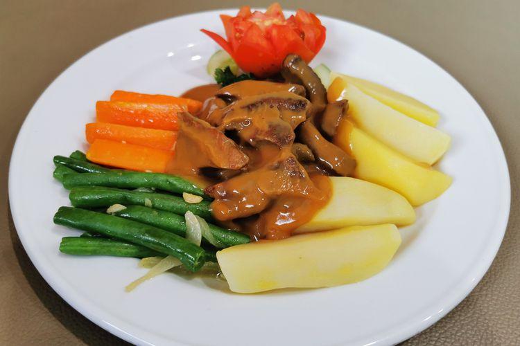 Ilustrasi bistik daging dengan aneka sayur sebagai pelengkap.
