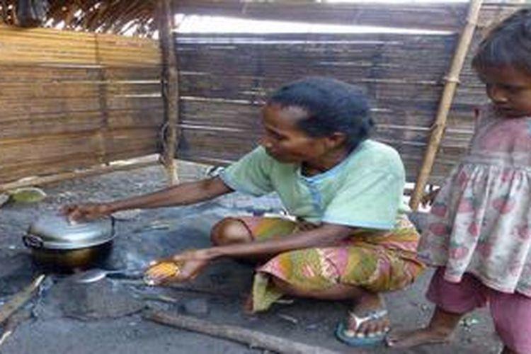 Ny Densi Lebi (45), warga Desa Lidi, Pulau Palue, Kabupaten Sikka, Nusa Tenggara Timur, Selasa (26/3/2013) ditemani cucunya sedang menanak nasi dengan menggunakan panci. Ny Densi bersama ribuan warga Palue lainnya mengungsi ke Kabupaten Ende, di Pulau Flores pada Desember 2012 terkait meningkatnya aktivitas Gunung Api Rokatenda. Pengungsi terutama kalangan ibu-ibu mengeluh, sebab mereka kekurangan peralatan memasak. Akibatnya, di antara pengungsi sering telat makan, sebab ketika satu keluarga sedang memasak, maka keluarga yang lain harus mengantre.