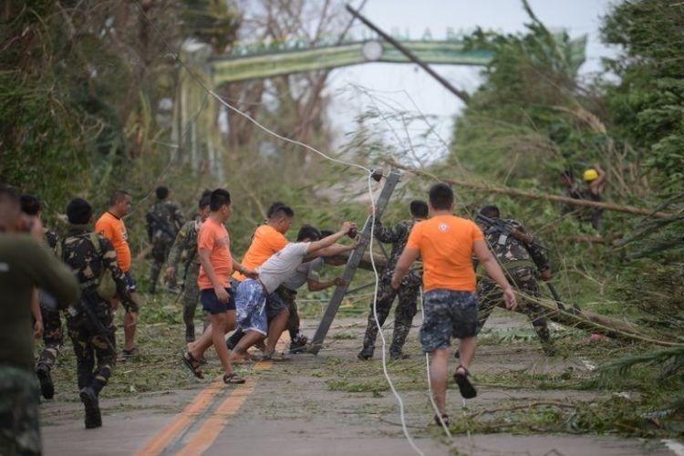 Petugas penyelamat membersihkan jalan dari puing-puing yang disebabkan oleh angin kencang siklon tropis Mangkhut di kota Baggao di provinsi Cagayan, sebelah utara Manila, Filipina, Sabtu (15/9/2018). (AFP/Ted Aljibe)