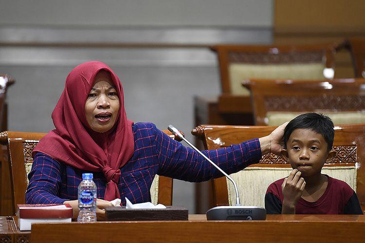 Terpidana kasus pelanggaran Undang-Undang Transaksi dan Informasi Elektronik (UU ITE), Baiq Nuril Maknun (kiri) didampingi anaknya menyampaikan tanggapan saat rapat pleno Komisi III DPR terkait surat persetujuan amnesti di Kompleks Parlemen Senayan, Jakarta, Selasa (23/7/2019). Rapat pleno tersebut untuk meminta tanggapan dari para fraksi terkait surat permohonan pertimbangan amnesti untuk Baiq Nuril dari Presiden Joko Widodo.