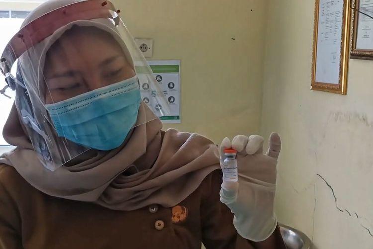 Seorang petugas kesehatan puskesmas di Indramayu saat menunjukan vaksin yang berhasil diselamatkan karena banjir.