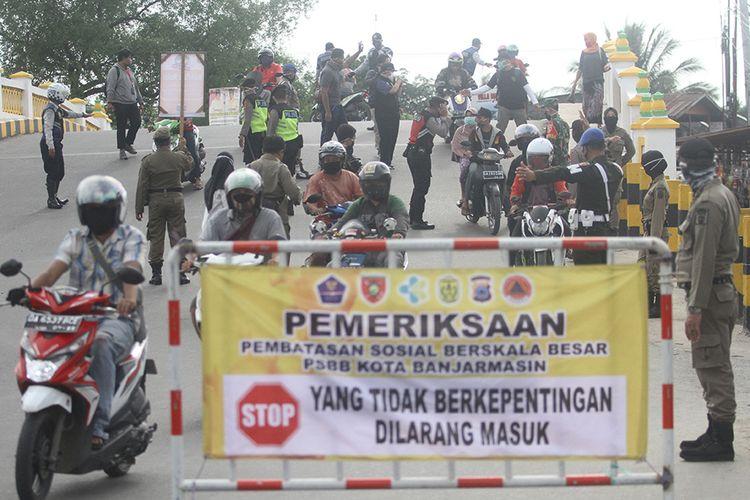 Petugas memeriksa identitas diri warga saat hari pertama Pembatasan Sosial Berskala Besar (PSBB) di perbatasan Kota Banjarmasin, Kalimantan Selatan, Jumat (24/4/2020). Pemerintah Kota Banjarmasin resmi menerapkan PSBB dalam rangka percepatan penangan COVID-19 selama 14 hari dimulai 24 April hingga 7 Mei 2020.