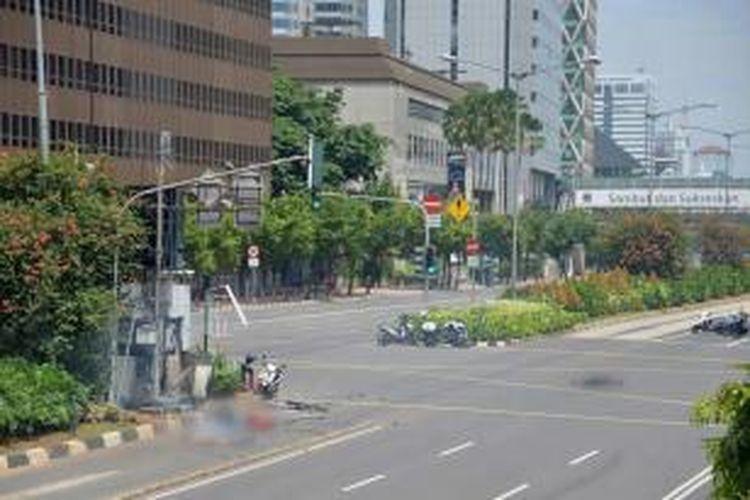 Tiga jenazah terlihat di jalan sekitar pos polisi yang rusak setelah ledakan menghantam kawasan Jalan MH Thamrin, Jakarta Pusat, 14 Januari 2016. Serangkaian ledakan menewaskan sejumlah orang, terjadi baku tembak antara polisi dan beberapa orang yang diduga pelaku.