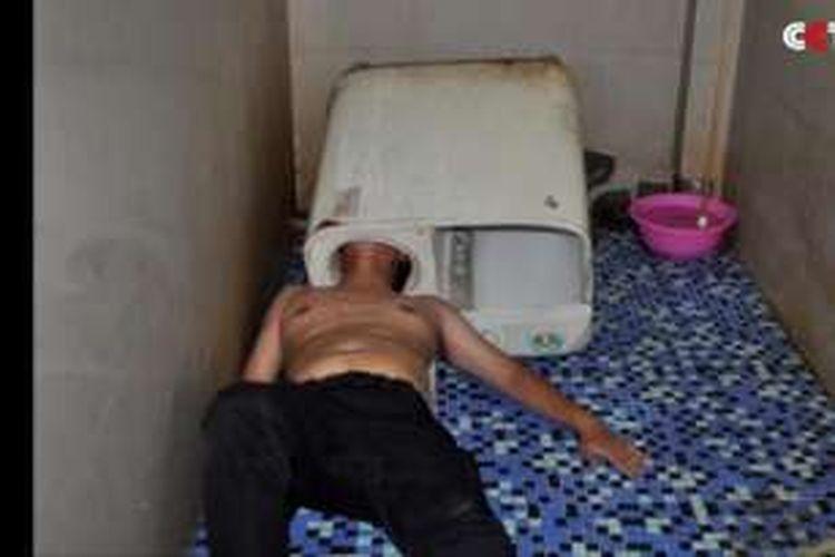Seorang pria di China mengalami musibah. Kepalanya tersangkut di dalam lubang mesin cuci.