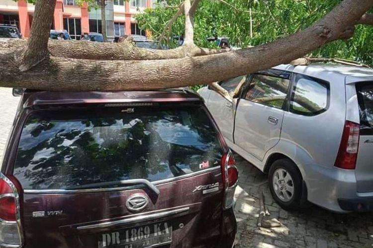 Suasana ketika mobil yang tertindih pohon tumbang akibat angin kencang di halaman parkir RSUP NTB