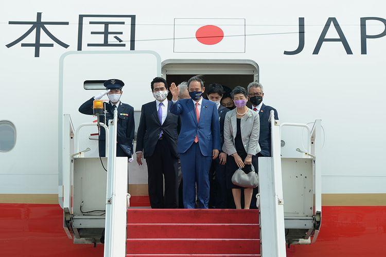 Perdana Menteri Jepang Yoshihide Suga (tengah) bersama Madam Suga Mariko (kedua kanan) melambaikan tangan setibanya di Bandara Soekarno Hatta, Tangerang, Banten, Selasa (20/10/2020). Lawatan kenegaraan tersebut dalam rangka meningkatkan hubungan bilateral antar-kedua negara.