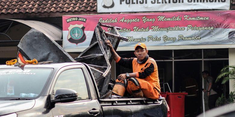 Petugas kebersihan mengangkut barang sisa perusakan dan pembakaran di Polsek Ciracas, Jakarta, Rabu (12/12/2018). Perusakakan dan pembakaran Polsek Ciracas yang dilakukan ratusan orang itu  terjadi pada Rabu dini hari (12/12/2018), yang dipicu ketidakpuasan atas penanganan kasus pemukulan seorang anggota TNI.