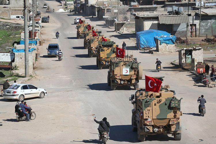 Iring-iringan kendaraan lapis baja berbendera Turki terlihat di zona demiliterisasi di Idlib, Suriah utara, Jumat (8/3/2019).