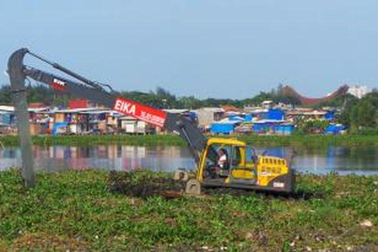 Pekerja menggunakan eskavator amfibi untuk membersihkan Waduk Ria Rio dari eceng gondok di Kelurahan Kayu Putih, Kecamatan Pulogadung, Jakarta Timur, Senin (2/9/2013).