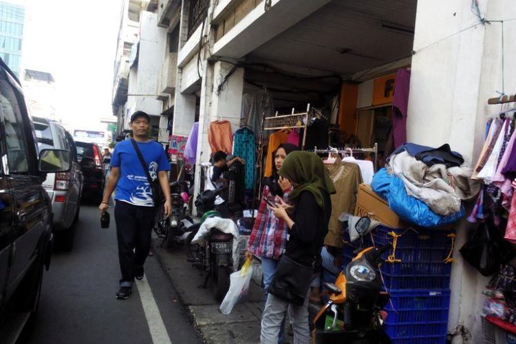 Salah seorang warga terpaksa berjalan di badan jalan lantaran area pedestrian di kawasan Pasar Baru Kota Bandung penuh ditempati PKL.