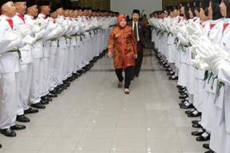 Risma berjalan di tengah-tengah Paskibraka Surabaya usai pengukuhan.
