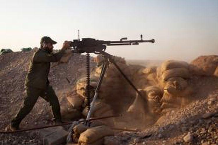 Seorang prajurit Irak menembakkan senapan beratnya ke arah pasukan ISIS dalam pertempuran di kota Tuz Khurmatu, provinsi Salahedin, MInggu (1/9/2014). Pasukan gabungan Kurdi dan milisi Syiah dikabarkan berhasil merebut kembali kota Sulaiman Bek.