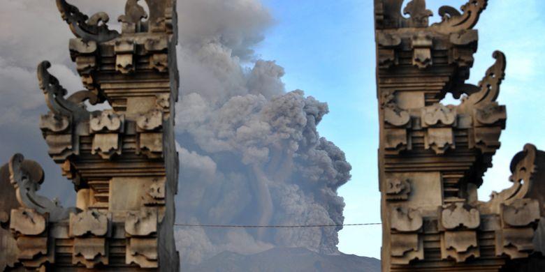 Erupsi Gunung Agung terlihat dari salah satu Pura di Kubu, Karangasem, Bali, 26 November 2017. Gunung Agung terus menyemburkan asap dan abu vulkanik dengan ketinggian yang terus meningkat, mencapai ketinggian 3.000 meter dari puncak. Letusan juga disertai dentuman yang terdengar sampai radius 12 kilometer.