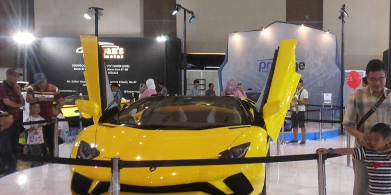 Pengunjung IIMS sedang berpose di depan salah satu Lamborghini yang dipajang di stan Prestige pada hari ketiga penyelenggaraan ajang Indonesia International Motor Show (IIMS) 2018 di JIExpo Kemayoran, Jakarta, Sabtu (21/4/2018).