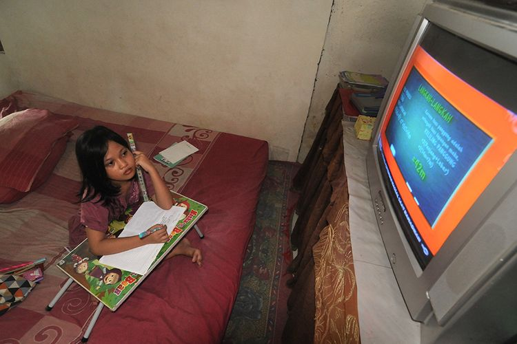 Seorang anak menyimak pembelajaran yang disiarkan melalui Televisi Republik Indonesia (TVRI) di Kelurahan Gladak Anyar, Pamekasan, Jawa Timur, Senin (13/4/2020). Kementerian Pendidikan dan Kebudayaan (Kemendikbud) menyiapkan 720 episode untuk penayangan Belajar dari Rumah selama 90 hari untuk PAUD hingga SMA melalui TVRI.