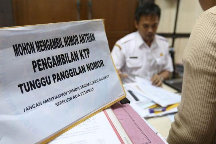 Salah seorang petugas terlihat sedang membantu warga dalam pembuatan kartu keluarga dan KTP di kantor Dinas Kependudukan dan Pencatatan Sipil di Tigaraksa Tangerang, Senin (31/8/2016). Sebagian besar warga mengurus e-KTP, KK, dan akta kelahiran.