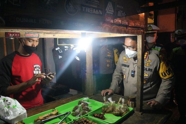 Kapolresta Banyumas Kombes M Firman L Hakim memborong sisa makanan di angkringan yang melanggar jam malam di Purwokerto, Kabupaten Banyumas, Jawa Tengah, Jumat(23/7/2021) malam.