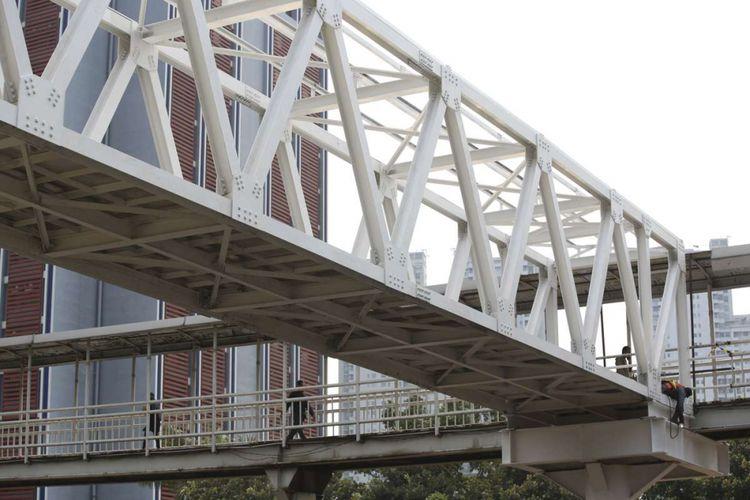 Pekerja menyelesaikan pembangunan jembatan penyeberangan orang (JPO) Halte Transjakarta Dukuh Atas di Jakarta Pusat, Rabu (4/10/2018). Pembangunan tersebut untuk menggantikan JPO lama yang posisi tiangnya berada di tengah ruas Jalan Jenderal Sudirman.