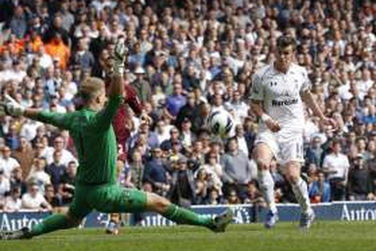 Gareth Bale (kanan) mencetak gol ke gawang Joe Hart saat Tottenham Hotspur bertemu Manchester City pada ajang Premier League di Stadion White Hart Lane, 21 April 2013.