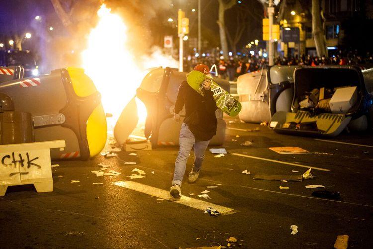 Seorang demonstran melarikan diri dari petugas polisi selama bentrokan setelah protes mengutuk penangkapan penyanyi rap Pablo Hasél di Barcelona, Spanyol, Rabu (17/2/2021).