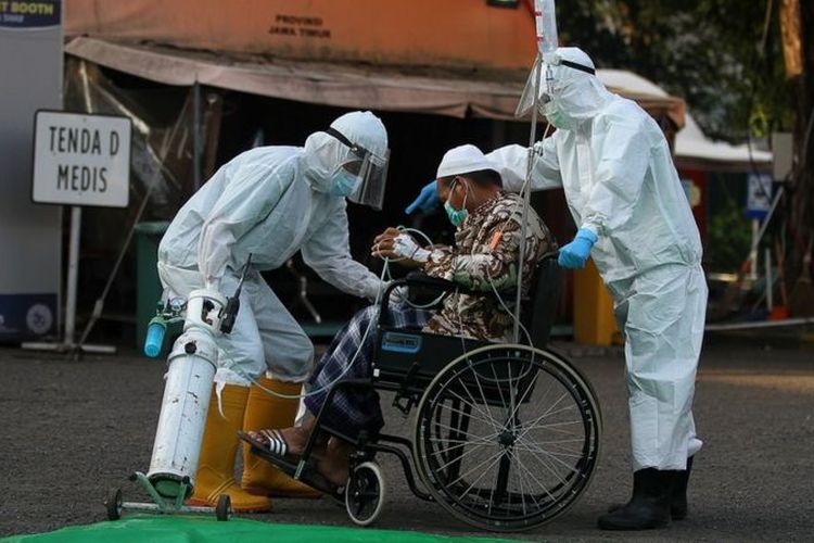 Tenaga kesehatan membantu seorang TKI yang mengindap Covid-19 usai salat Idul Fitri di halaman Rumah Sakit Lapangan Indrapura Surabaya, 13 Mei 2021. Sekitar 30 TKI dirawat di rumah sakit itu saat lebaran lalu.