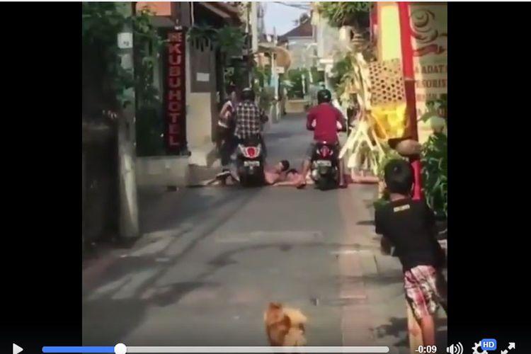 Salah seorang wisatawan yang sedang berjemur di jalan Bali tampak digilas pemotor.
