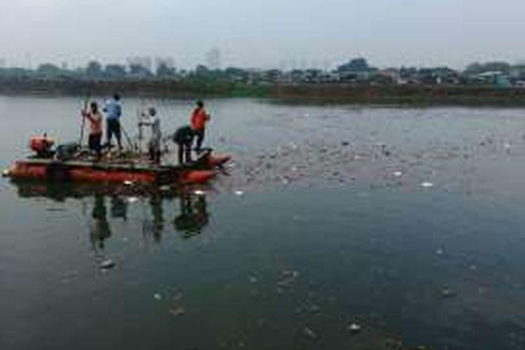 Para pekerja dari Unit Pengelola Kebersihan (UPK) Badan Air Dinas Kebersihan DKI di Waduk Ria Rio, Pulogadung, Jakarta Timur turun dengan perahu untuk membersihkan sampah yang mengotori waduk setelah hujan. Senin (19/9/2016).