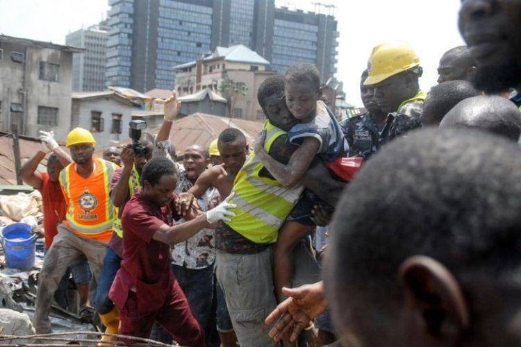 petugas  menyelamatkan seorang anak di lokasi sebuah bangunan yang runtuh di Lagos, Nigeria, Rabu (13/3/2019). (AFP/SEGUN OGUNFEYITIMI)
